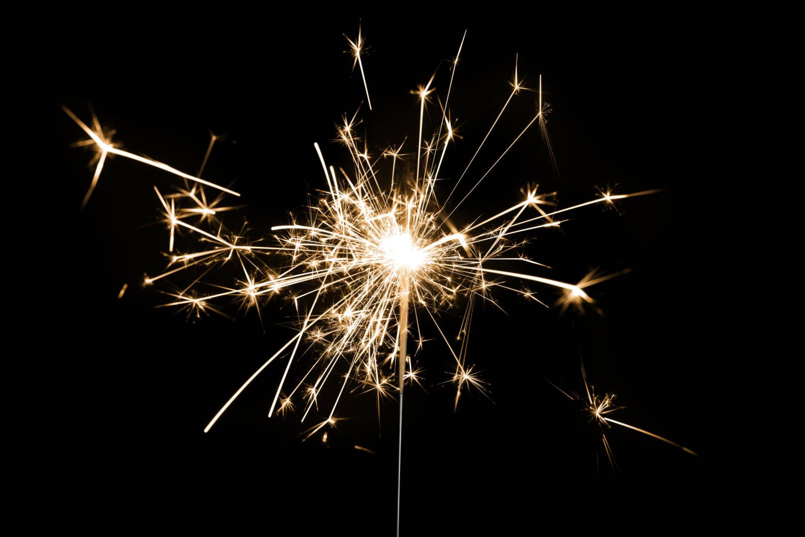 Burning sparkler on a black background wallpaper